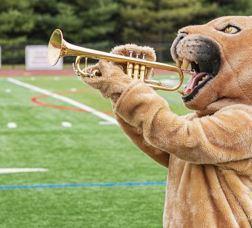 A cougar custom made mascot pretending to play a trumpe