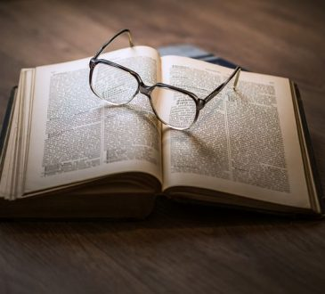 a pair of prescription glasses and a book