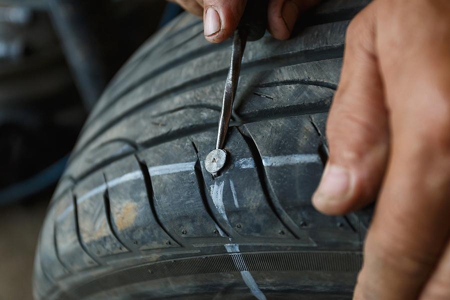 man fixing a car's tire