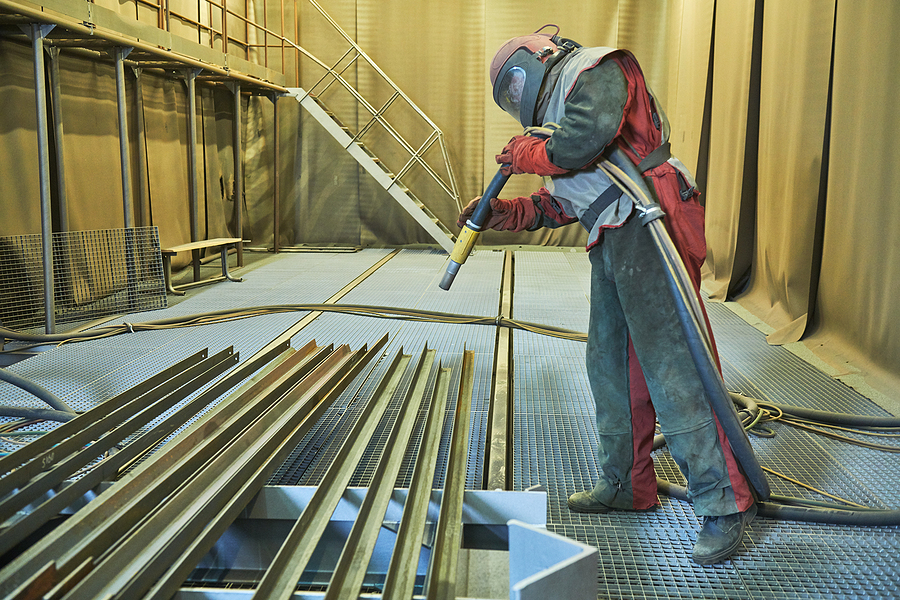 Worker makes sand blast cleaning of metal detail